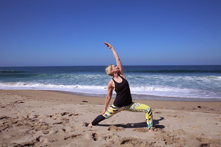 Lisa in warrior pose on the beach